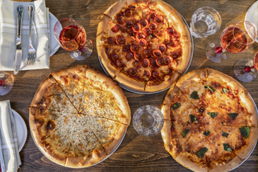 Overhead view of three pizzas with rosé at Rosie Cannonball