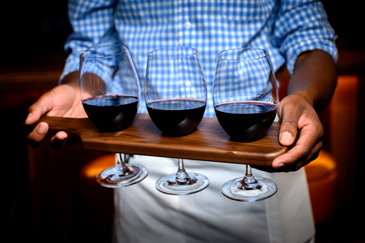 Person holding flight of three red wines at Walla Walla Steak Co.
