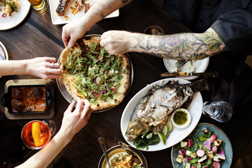 Pizza and whole fish on wood table at Young Joni