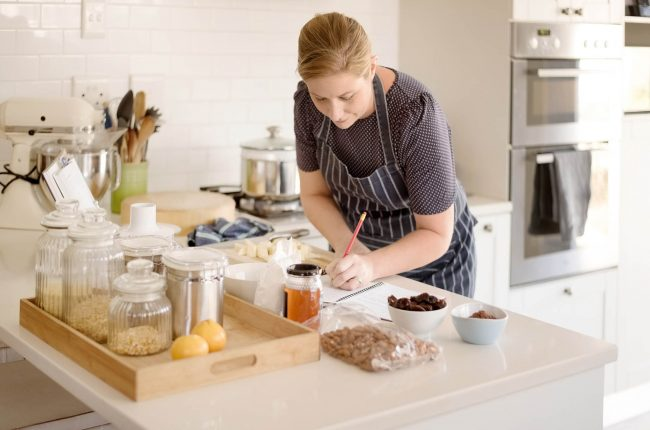 Woman in kitchen with notebook, surrounded by ingredients, developing food recipe