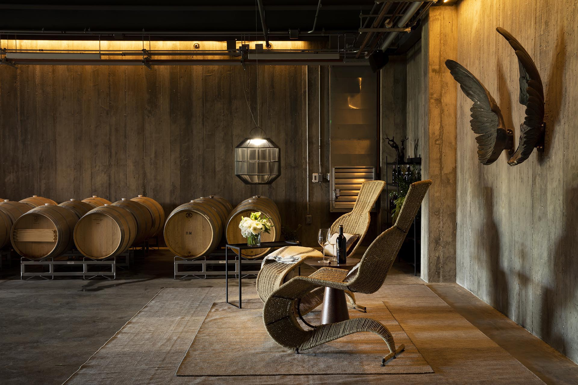 Interior seating area of Theorem Vineyards, with wood-lined room, oak barrels and wicker chairs