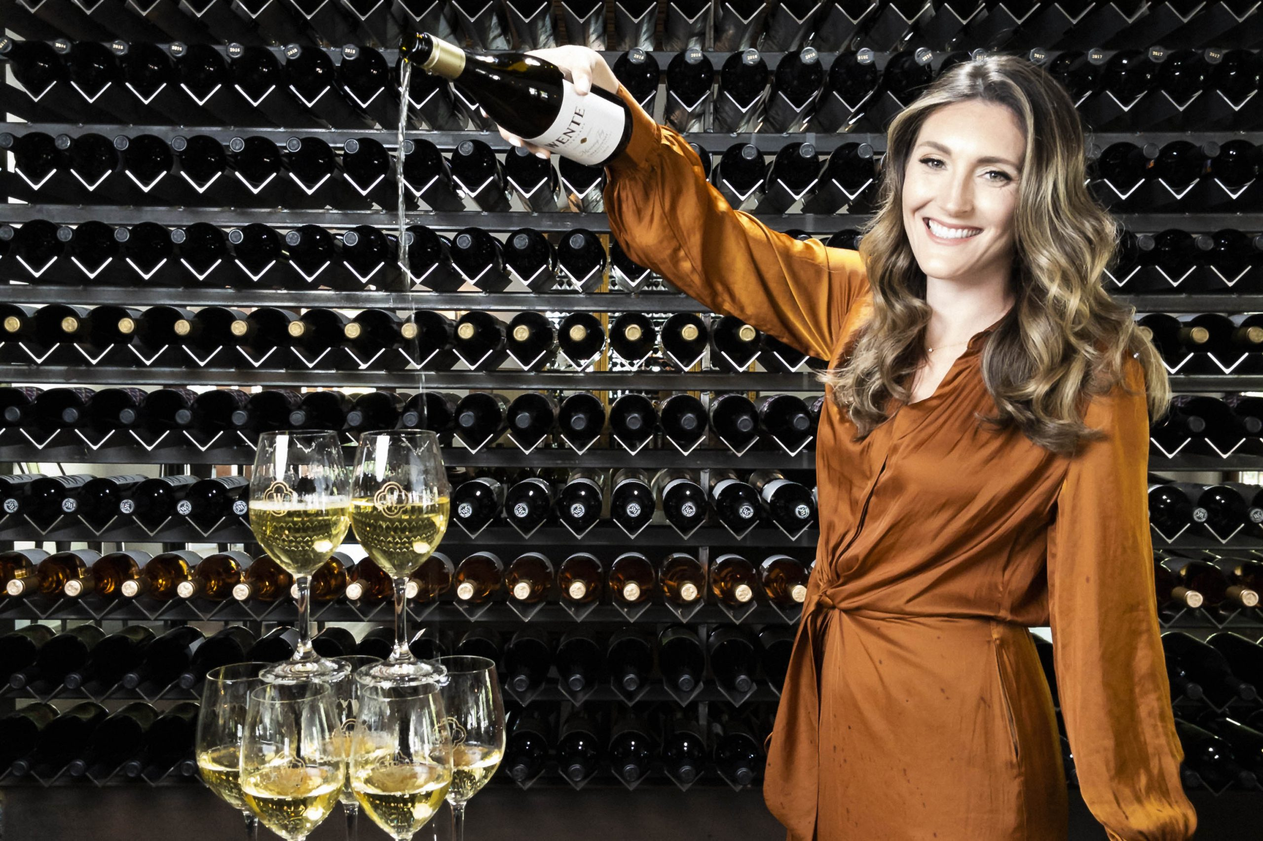 Aly Wente, standing, pouring white wine into pyramid of wine glasses