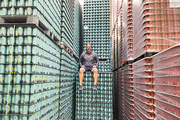 Bill Shufelt sitting on pallets of Athletic's non-alcoholic beer