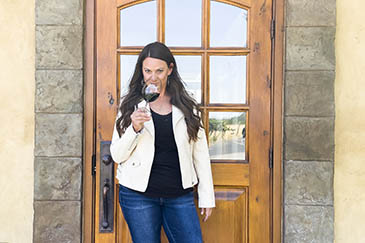 Sadie Drury holding a glass of red wine outside her tasting room