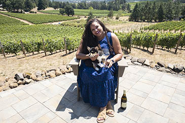 Tiquette Bramlett holding her dog and a glass of wine on a patio outside the vineyard