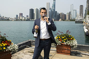 Todd Nelson standing on dock by water with skyline in background, holding wine