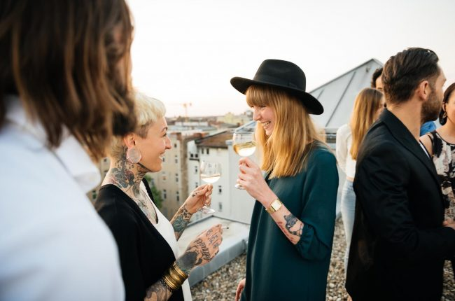 Two tattooed young women drinking white wine at a rooftop party
