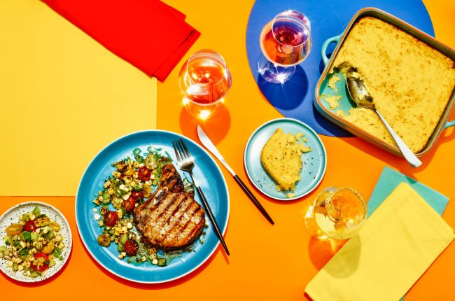 Pork chops with corn pudding and wine pairings on orange, yellow, red and blue backdrop