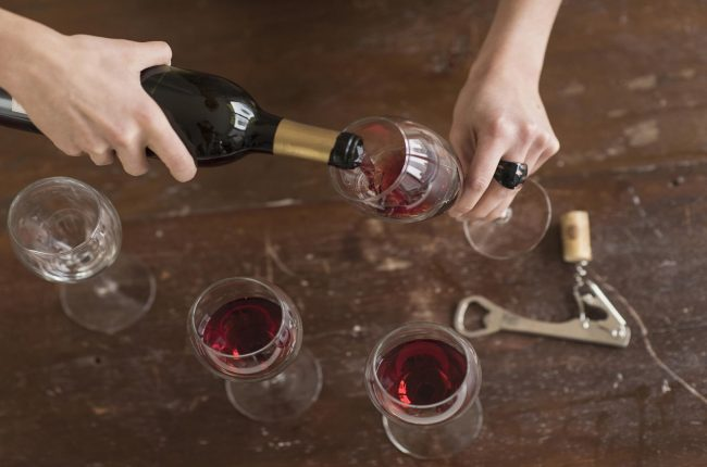 Elevated view of woman pouring red wine_GettyImages-539669257_1920x1280