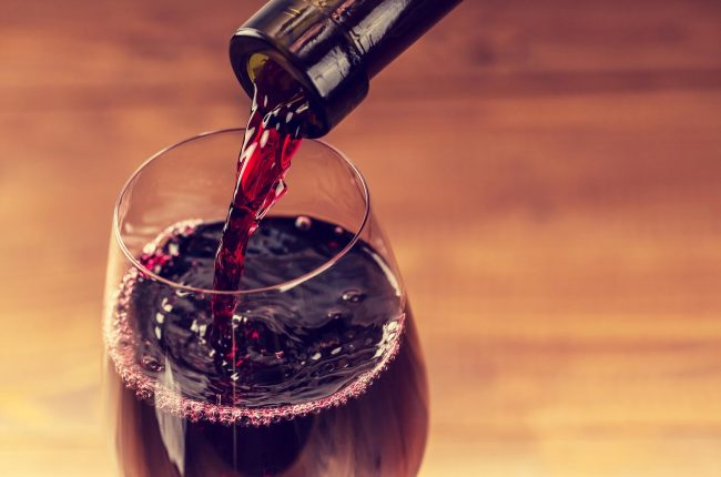 Pouring red wine into the glass against wooden background_GettyImages-492609770